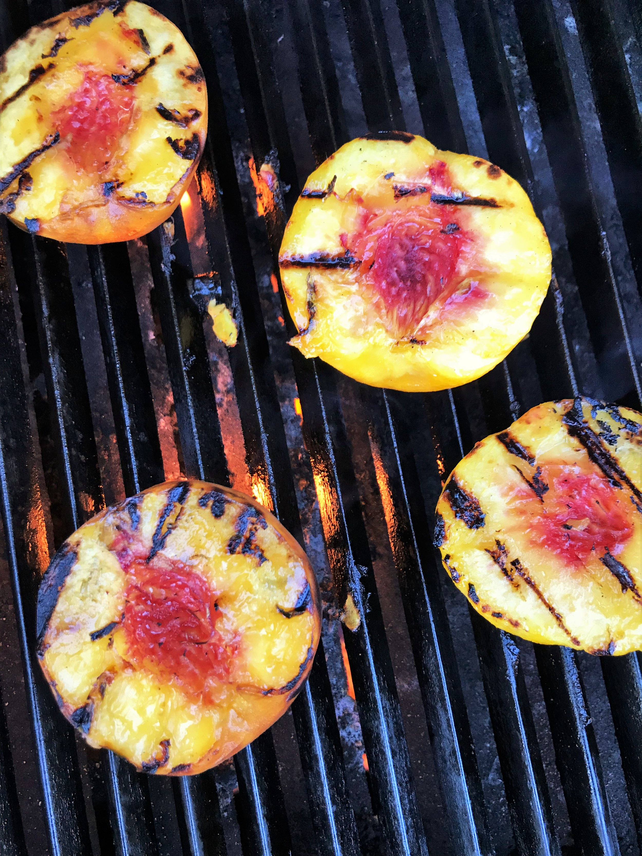 Fresh peaches on the grill, ready to be drizzled with the Aleppo-tequila honey sauce.