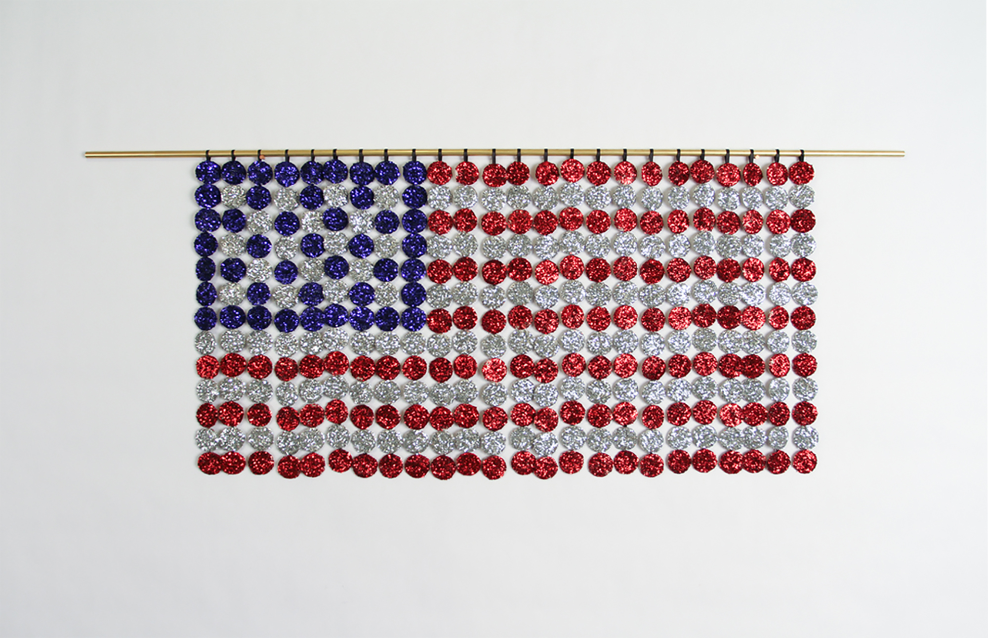 "Flag   ,  2017. Communion wafers covered in glitter, cotton, brass. 14.5"" x 36"" x .5""."