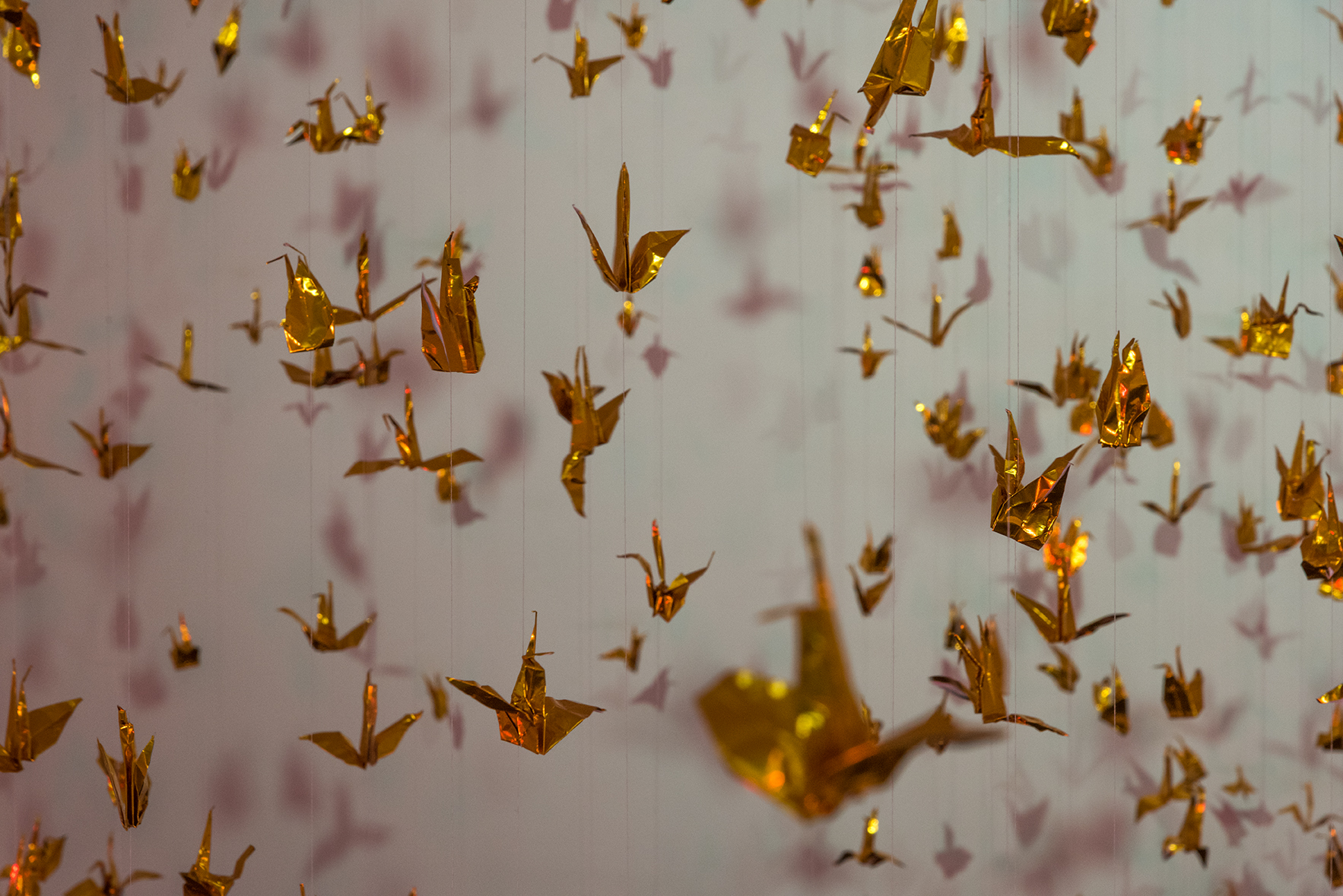 Isabelle Harada  W=Fd , 2016 Variable dimensions 999 foil origami cranes, thread, mylar gels