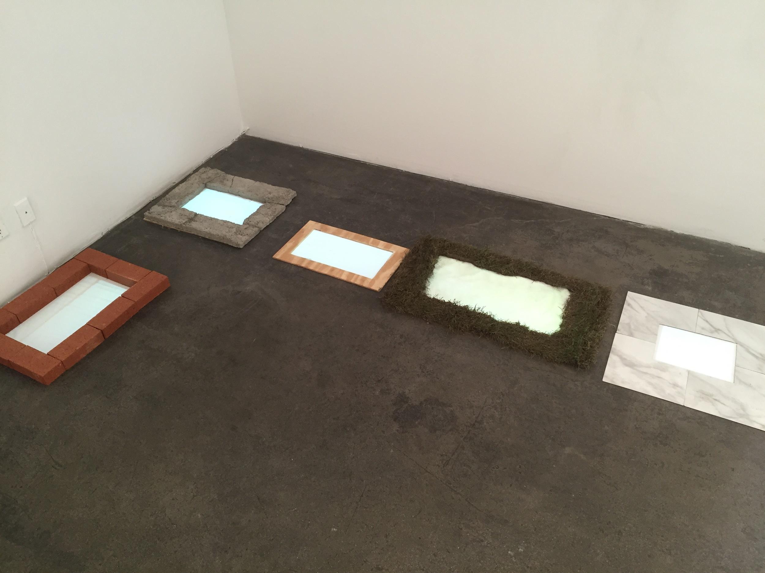 Isabelle Harada  Find your Feet , 2016 5 channel video installation Concrete, wood, brick, sod, linoleum, projection  Variable arrangement