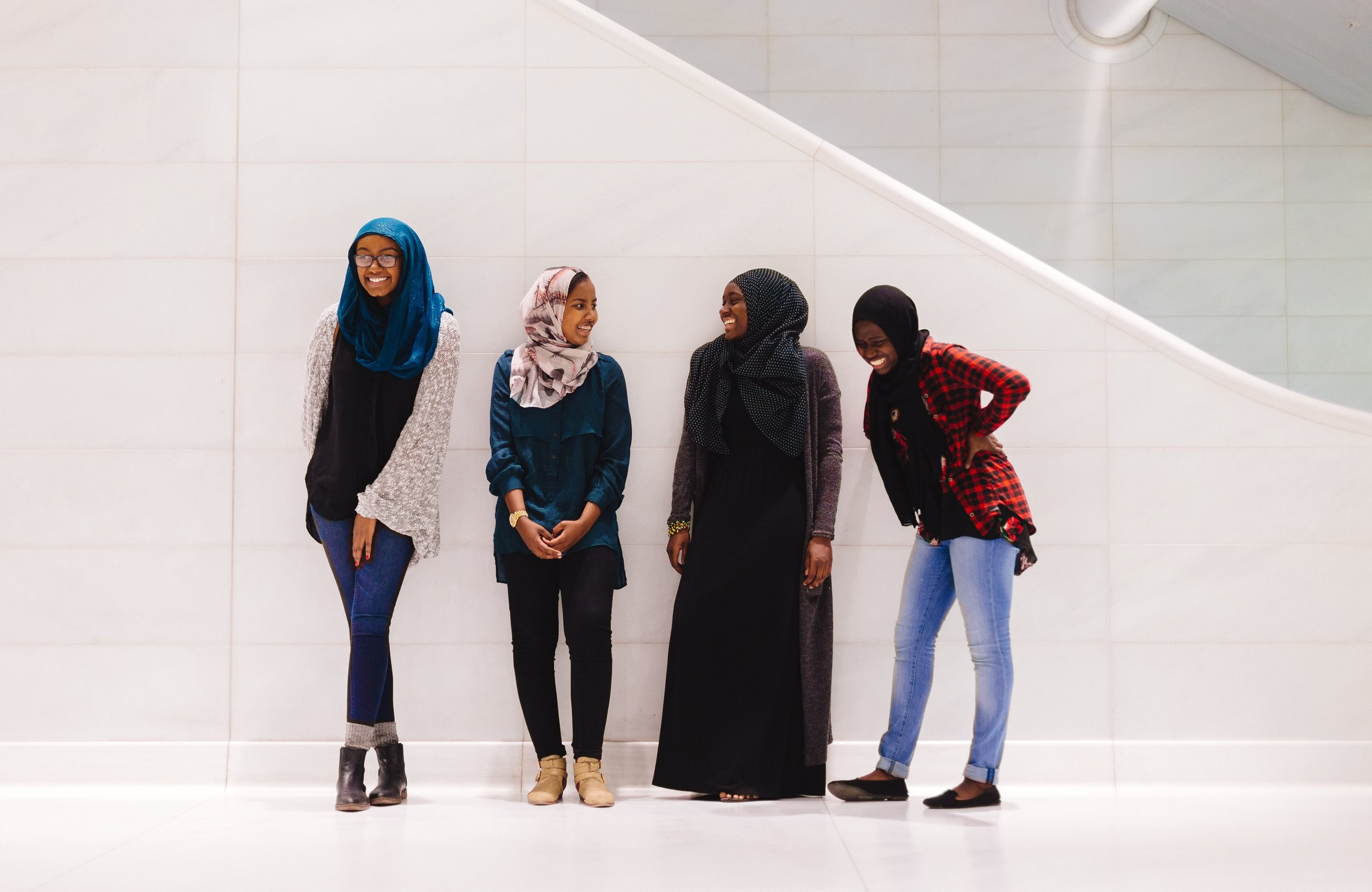 NYU students Bayan Abubakr, Fadumo Osman, Isatou Daffeh, and Mariyamou Drammeh share a laugh in a train station in New York City. Photo by Emilio Madrid-Kuser