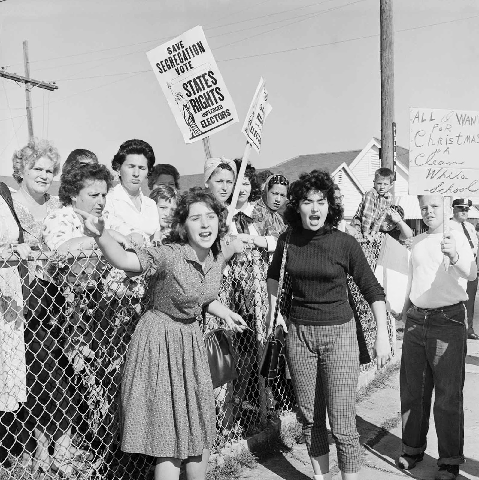 "Women at William Franz Elementary School yell at police officers during a protest against desegregation of the school. Some carry signs stating ""All I Want For Christmas is a Clean White School"" and ""Save Segregation Vote, States Rights Pledged Electors""."