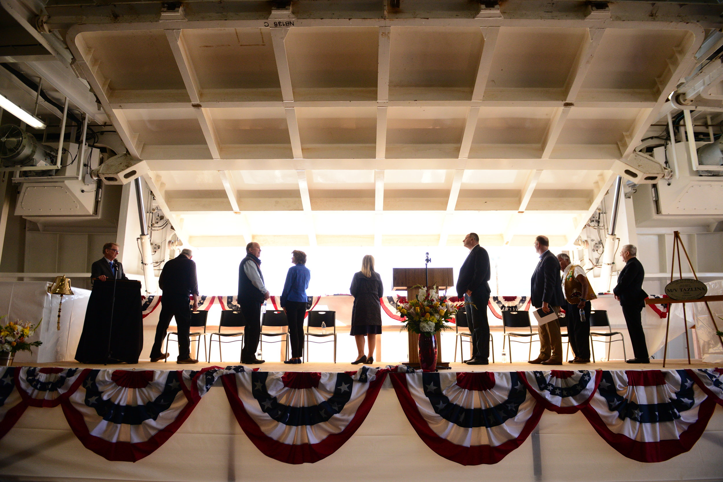 Representatives including Gov. Bill Walker, First Lady Donna Walker, Senator Bert Stedman, and Senator Lisa Murkowski are silhouetted as the rear loading dock of the Alaska Marine Highway's newest vessel, the M/V Tazlina, is opened to the sun during the ferry's christening at the Vigor Shipyard in Ketchikan. August 2018.