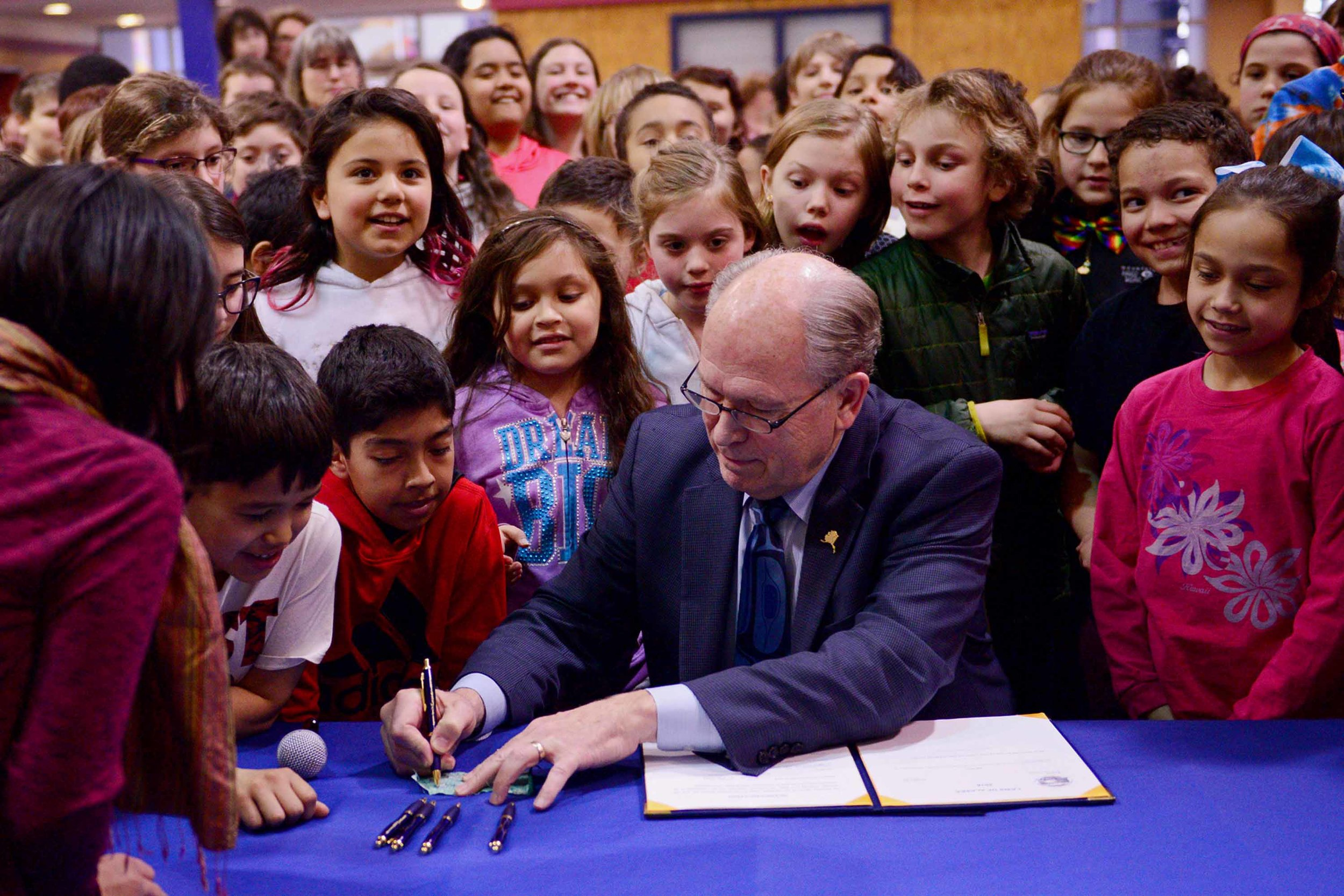 In Juneau, Harborview Elementary School students crowd around Gov. Walker as he signs House Bill 287, allocating $1.3 billion to early fund Alaska's schools for two years. May 3, 2018.