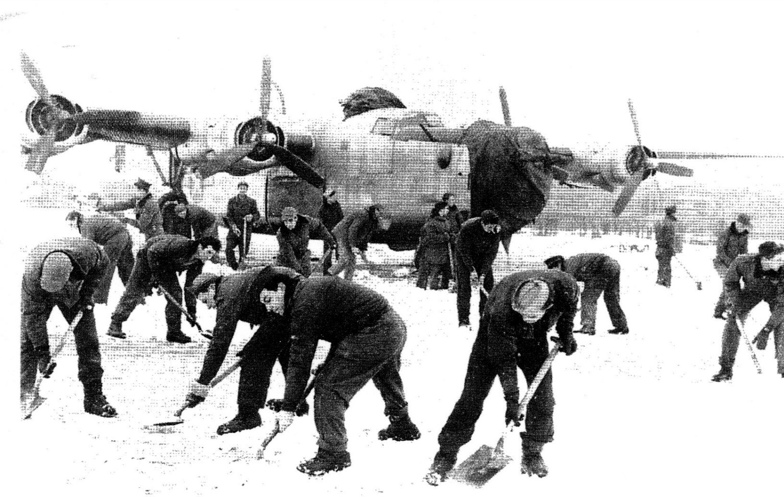 The 445th, including the Heitz Crew, shovels snow off the tarmac in December, 1944. Harrison front center right.