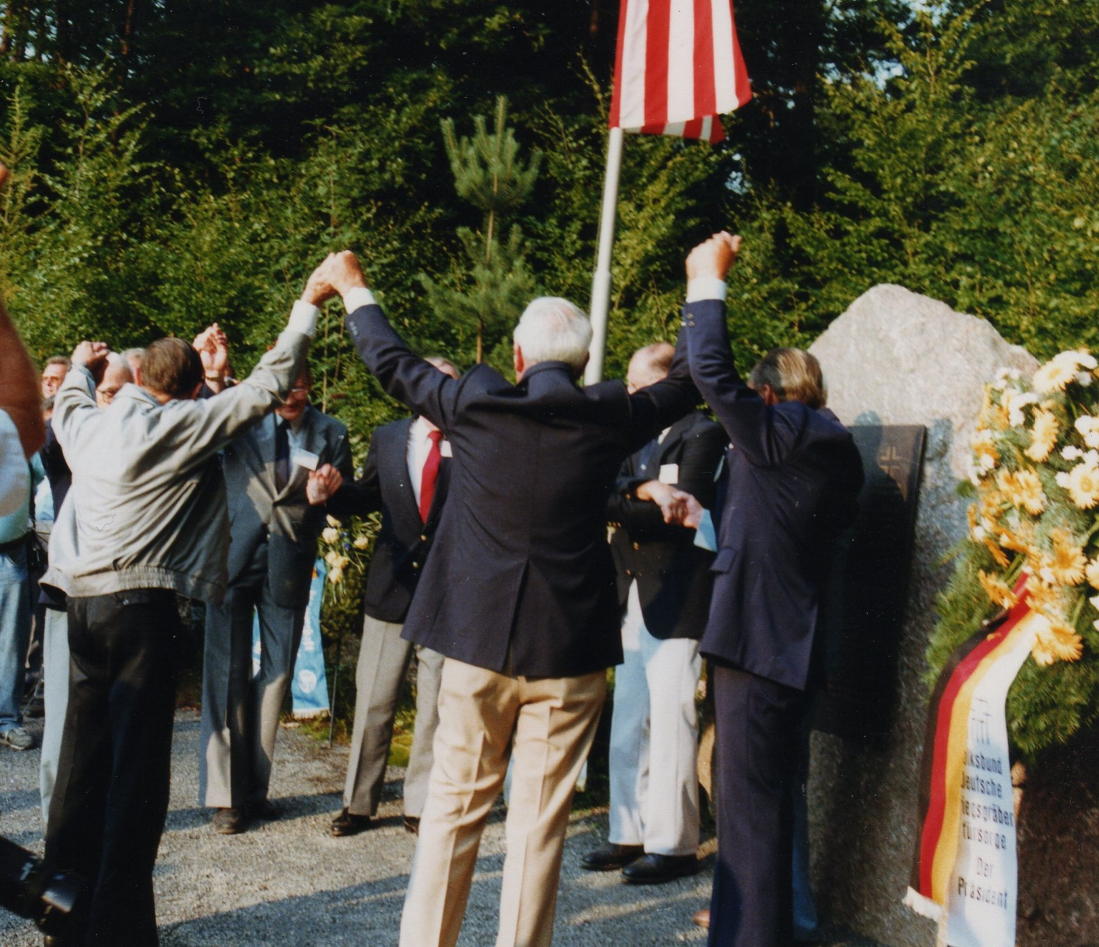German and Amercan former enemies who fought in the Kassel Mission raise their hands in victory over war, celebrating new friendships after together unveiling the three plaques at the Memorial at the dedication ceremony on 1 August 1990. Photo courtesy Walter Hassenpflug.