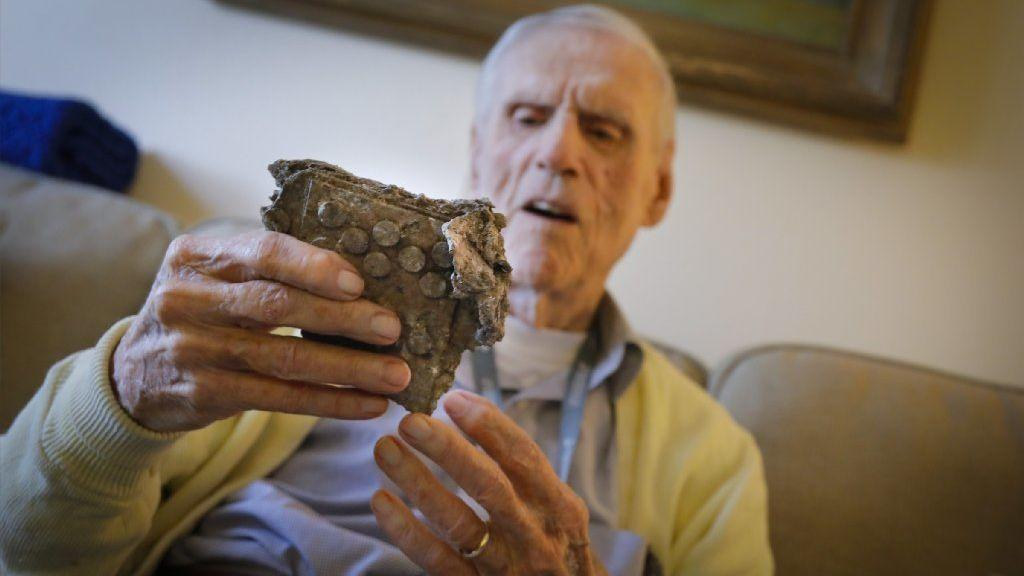 Alan Carlton looks at one of the pieces of his downed B-24. (Howard Lipin/Union-Tribune)