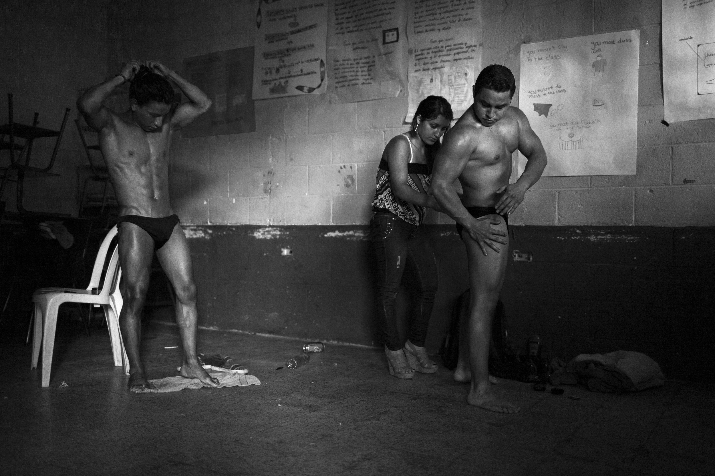 Competitors have help applying bronzer before the Gimnasio La Fábrica bodybuilding contest in Antigua, Guatemala.