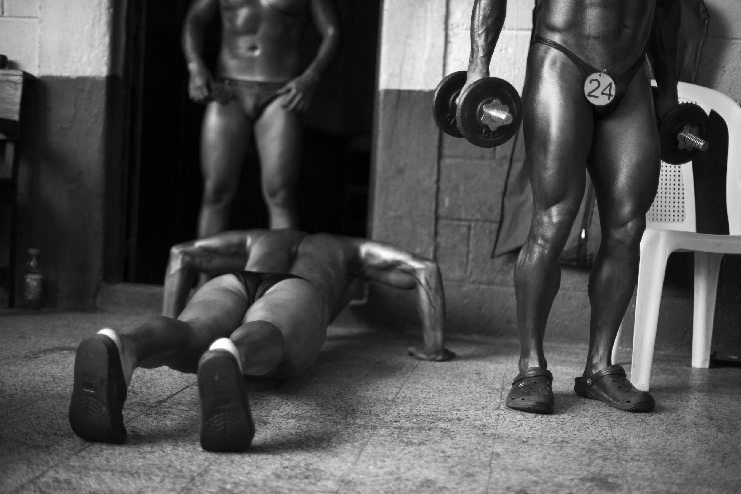 Competitors look for a pre-contest pump before the Gimnasio La Fábrica bodybuilding contest in Antigua, Guatemala.