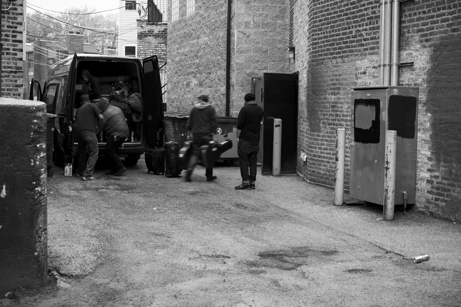 5PM—Loading the van is an art, a game of tetris with drums, guitars, amps, and luggage. Load it wrong and it won't fit, worse, something will break on the drive. Here, the band gets help unloading from venue employees.