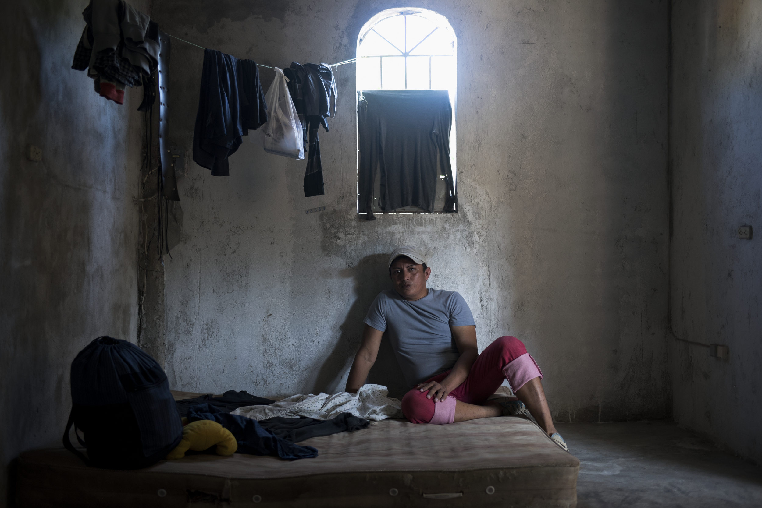 Danilo Munguia, 34, from El Salvador, in the one room house he shares with three other people. Danilo is transgender but had all of his clothing robbed while staying at a shelter in Tapachula. Finding a safe place to sleep is a daily challenge. He is sharing this small house with three other migrants from El Salvador (a mother and son and one other woman), but he often feels unsafe as one of the women has a violent boyfriend who comes to the house for days at a time.