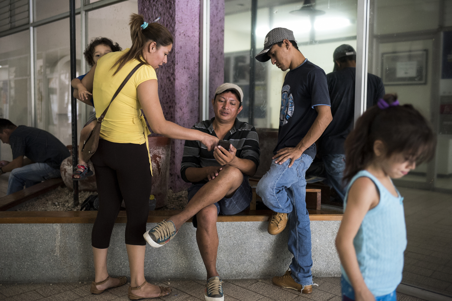 Danilo and two other asylum seekers sit and sit outside the offices where they are waiting to hear about the status of their applications.The woman on the left attended cosmetology school and is showing Danilo and his friend, Nildeson Ismael, photos from school. Danilo dreams of attending cosmetology school when he makes it to Tijuana.