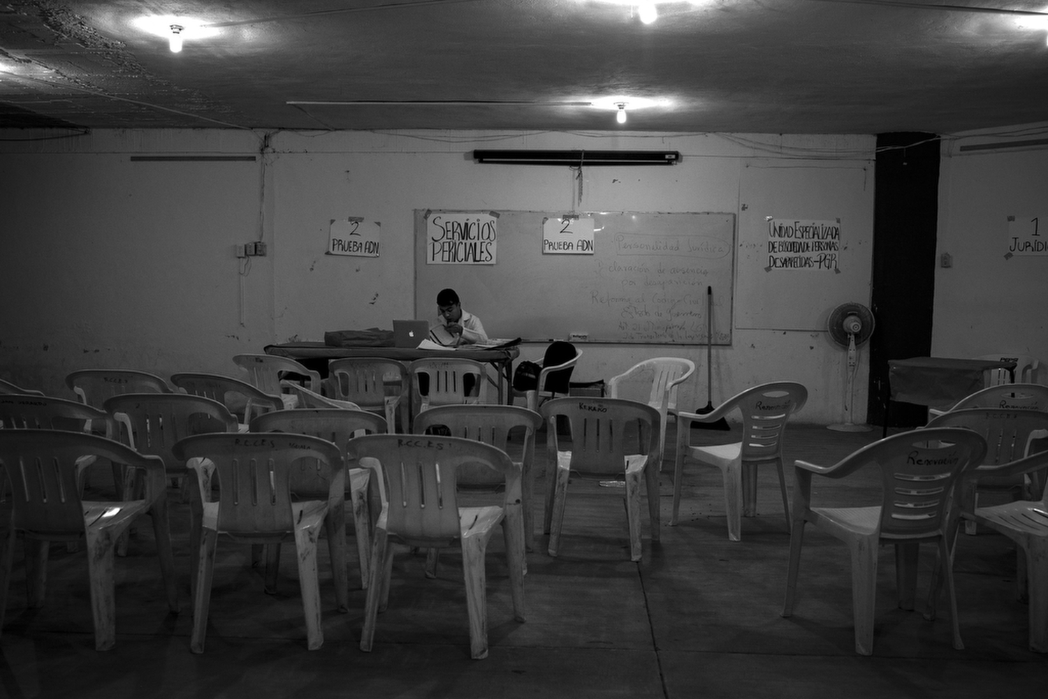 A worker with the    Procuraduría General de la República  (Mexico's Attorney General) sits in a church basement taking DNA samples. As relatives took to the hills to search for the students' remains numerous mass graves were found in the area. Families with missing relatives tested their DNA to help identify remains.