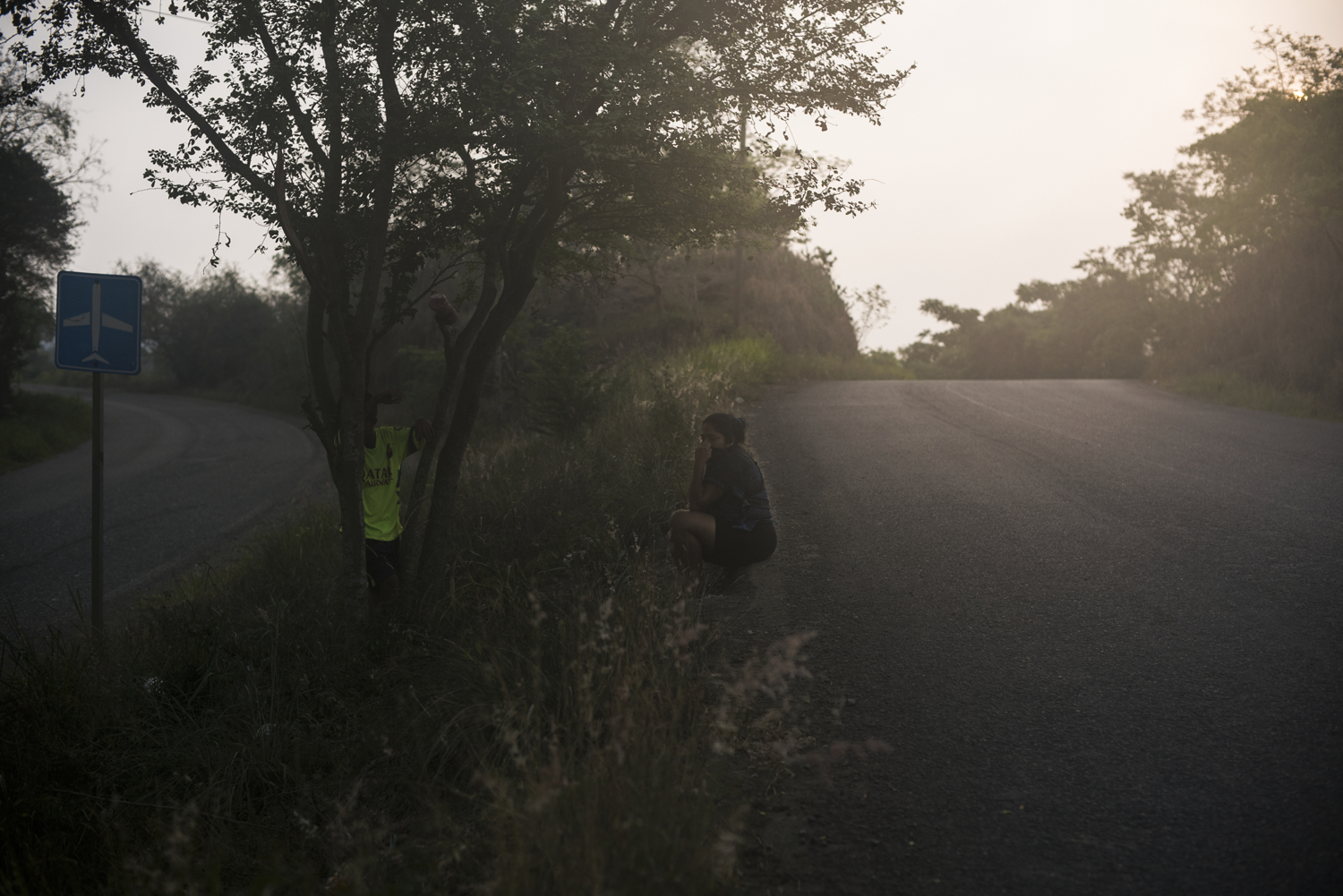 A woman and her son wait for a bus on May 25, 2016 outside of Poza Rica, Veracruz.   Just a few miles from Haliburton's headquarters in Poza Rica, the fields along this road are a favorite for cartels to dump dead bodies. The criminal organizations are increasingly dependent on black market oil revenue and are rumored to have connections with many of the subcontractors who do business with the major oil companies operating in the area.