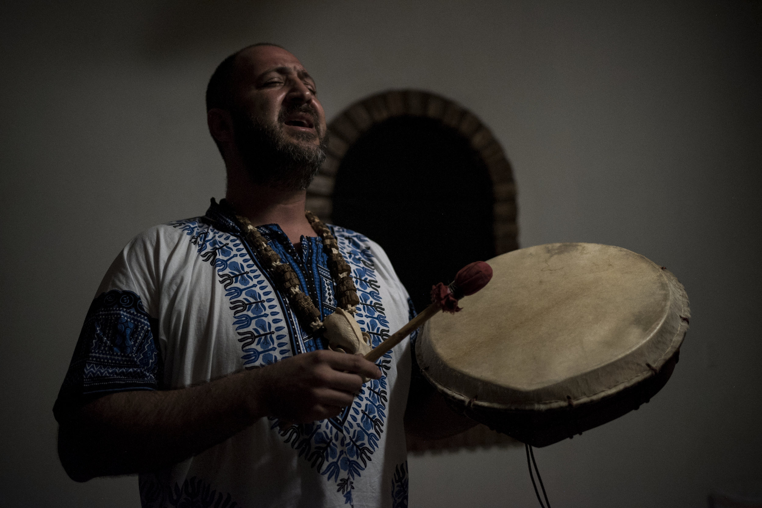 A shaman plays traditional music for Andrew Ortega while he is on Ayahuasca.