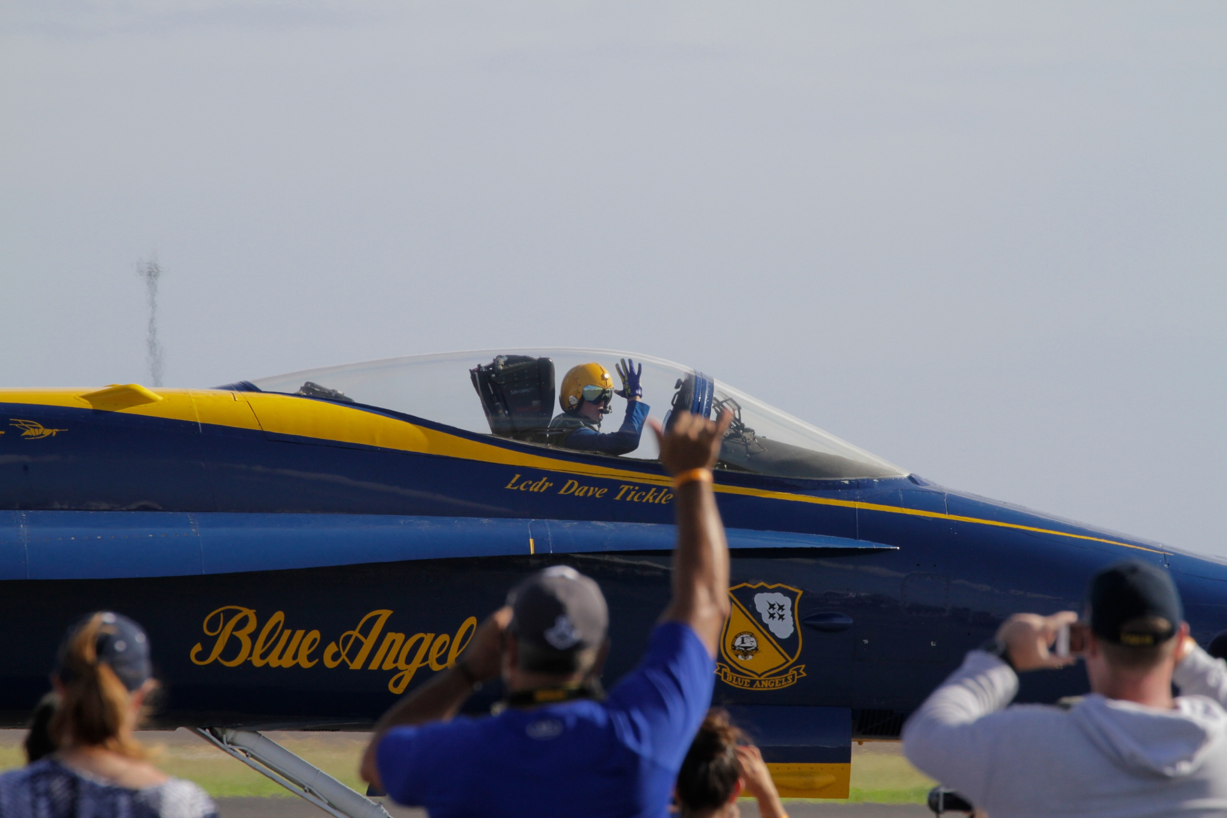 A pilot waves to the crowd and gets a shaka back.
