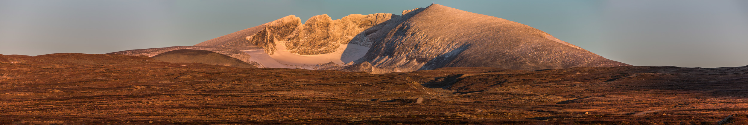Snøhetta  mountain at  Dovrefjell in Norway .  This panoramic photo is put together by five images captured October 2 at sunrise. I went on my bike very early that morning in the dark on the remote road to find a location to take these shots. I knew the first snow was there on the mountain already and the combination with autumn colors was a very nice view.