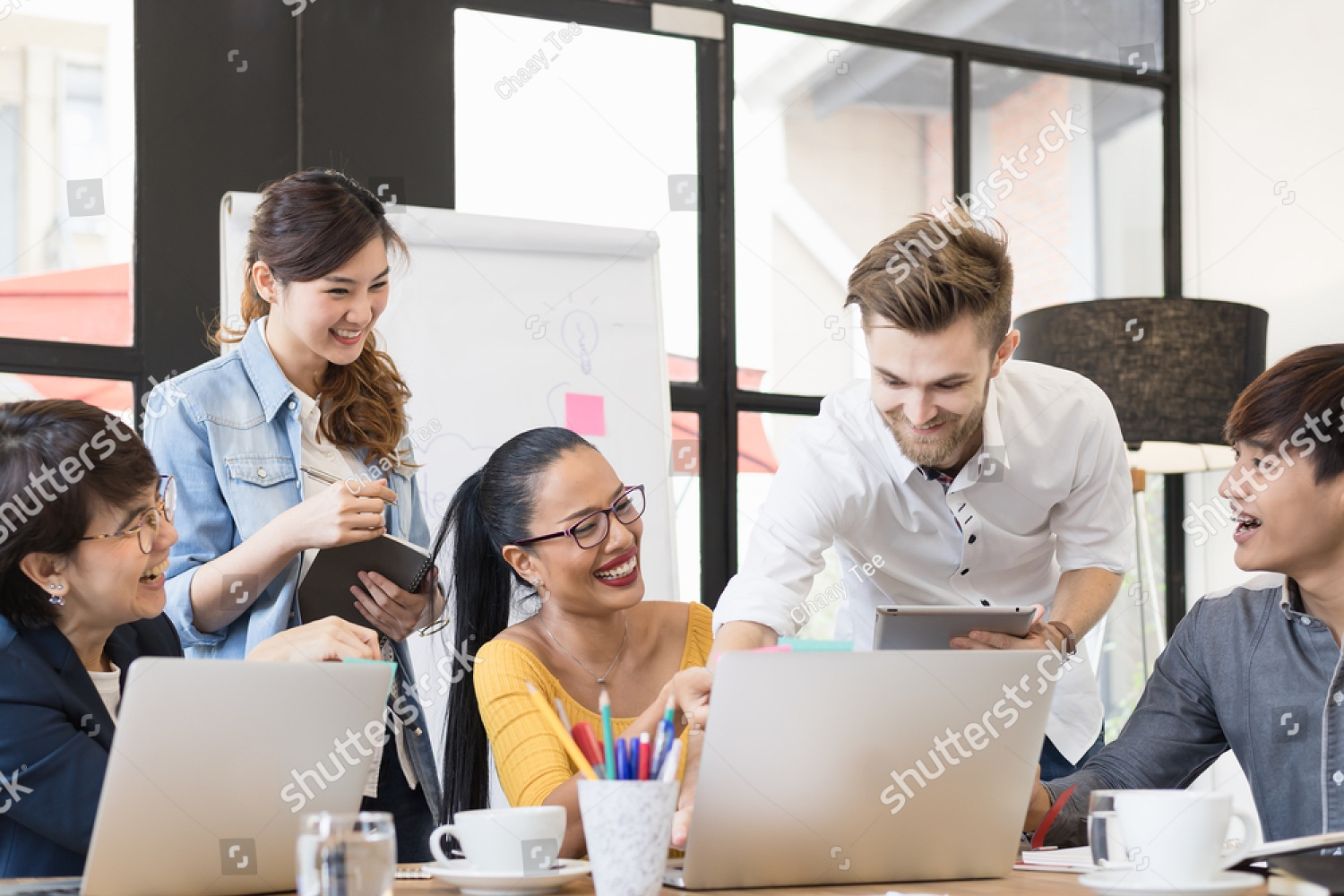 stock-photo-multiethnic-group-of-happy-business-people-working-together-meeting-and-brainstorming-in-office-598400243.jpg