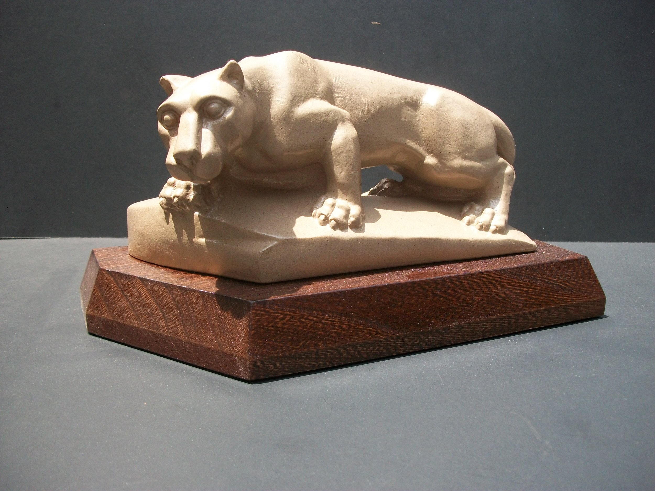 This piece is made in two separate parts, both made out of the resin with pecan shell flour. The finish on the nittany lion is done with a base coat of paint with a speckled spray on top. The base was finished with a stain and polished.