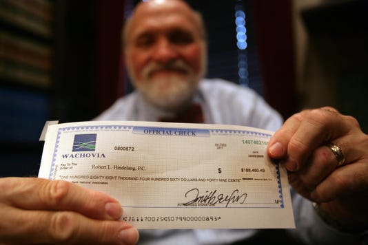 Smiling donor handing over a check