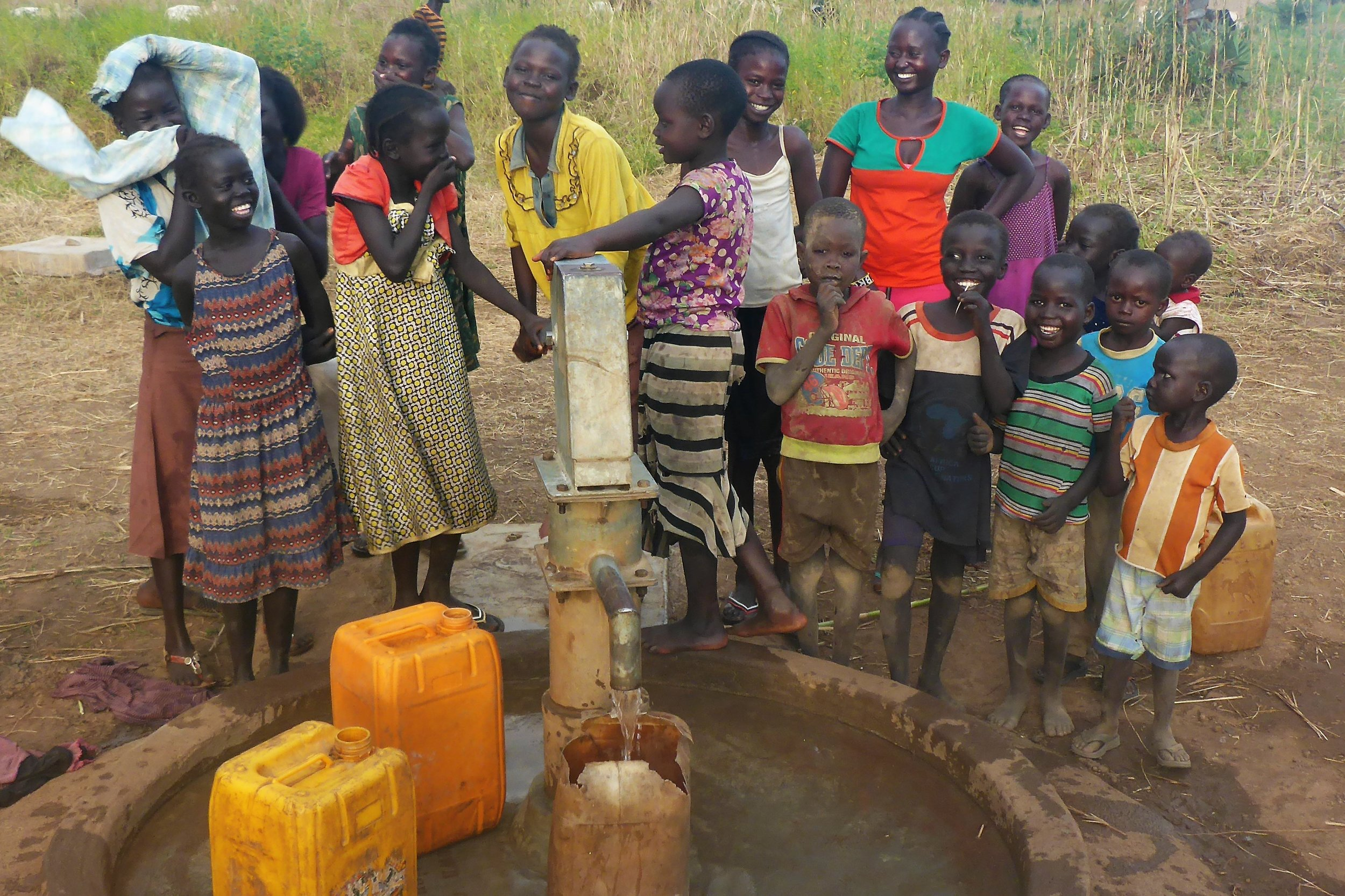 Children gather around newly rehabilitated well in Jur River County.
