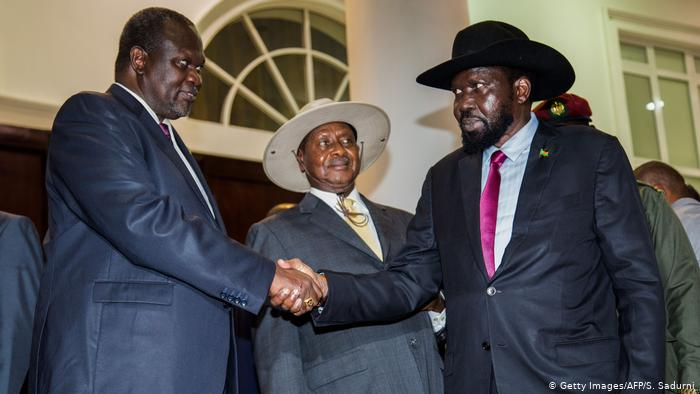 President Salva Kiir (right) and opposition leader Riek Machar (left) shake hands while Ugandan President Yoweri Museveni looks on.