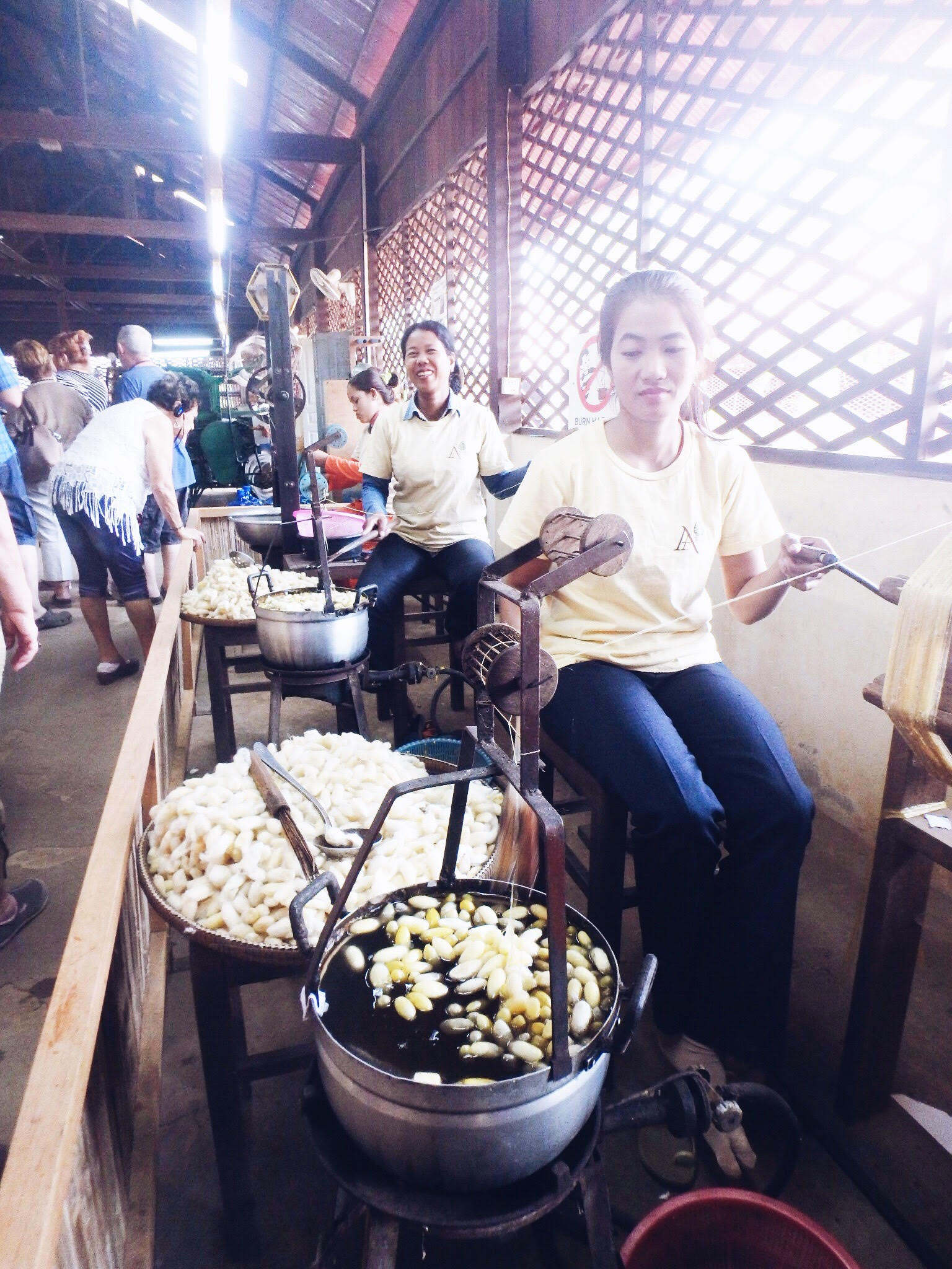 A happy employee boils the cocoons and then slots them onto a wooden stick that is used to pull the silk. Each cocoon is made of one continuous thread of silk.