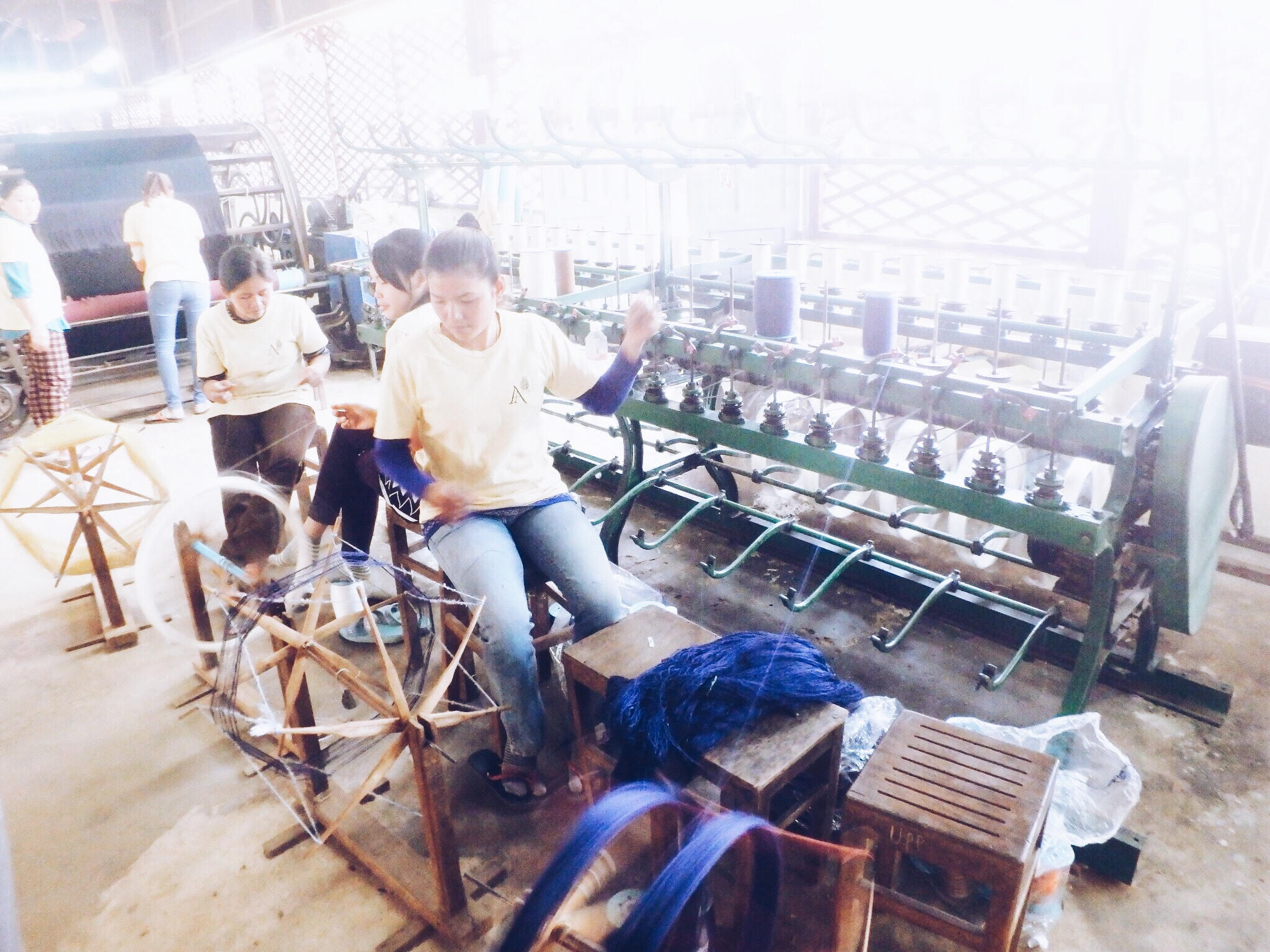 The thread is transferred from the large wooden spinning   wheels to spools.