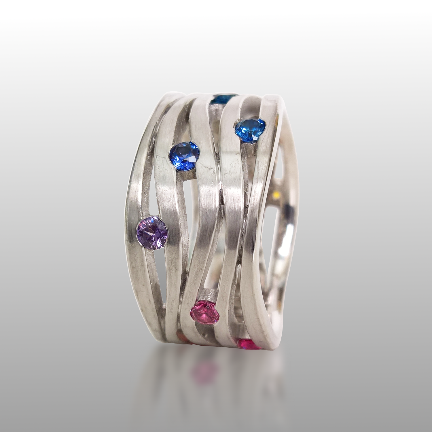 Contemporary platinum wave ring 'Lamello' with rainbow sapphires by Pratima Design Fine Art Jewelry Maui