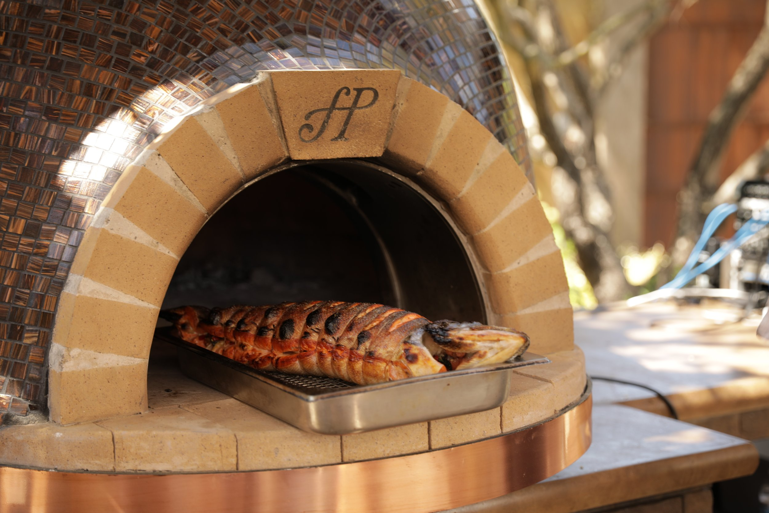 Cooking a trout in a Forno Piombo wood fired oven