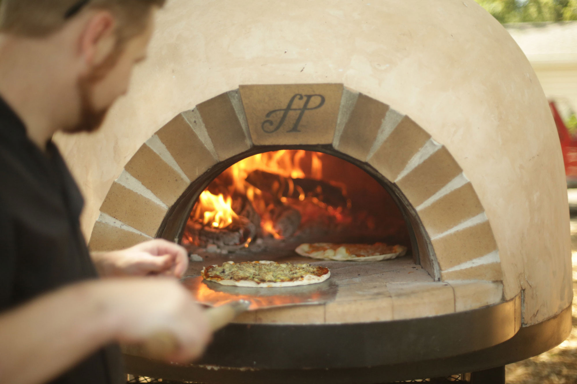 Chef Todd Thompson cooking pizza in a Forno Piombo pizza oven