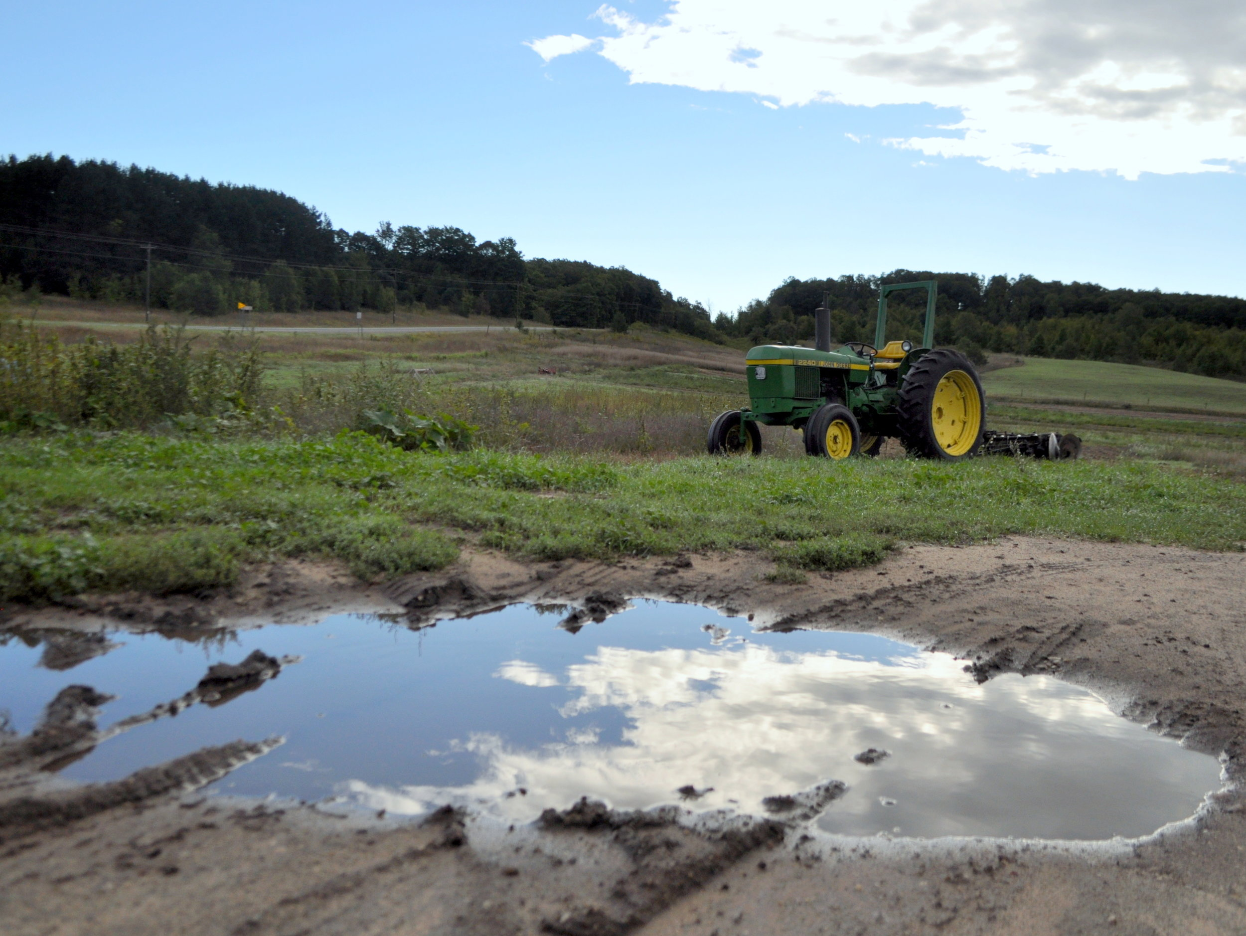 A puddle reflects the sky and a tractor takes five.