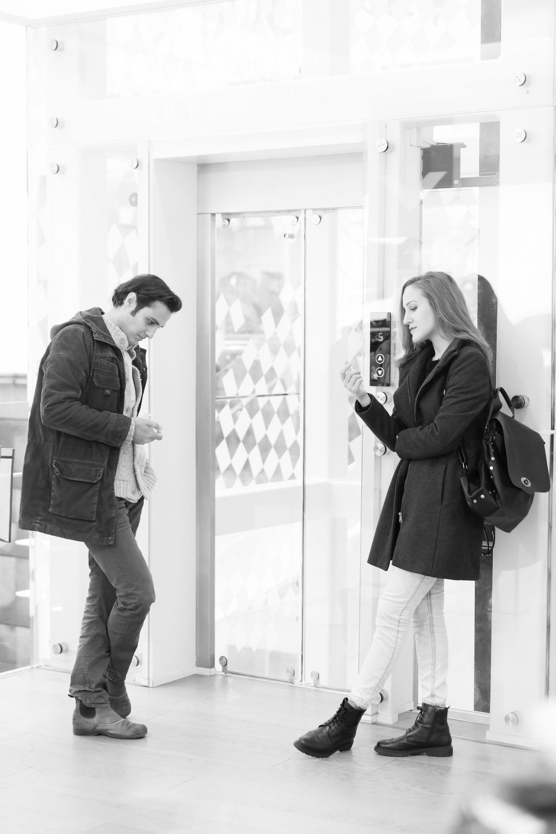 Man and woman awkwardly waiting for an elevator