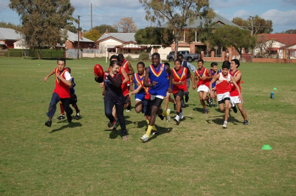 Students playing Australian Rules Football on the school oval.