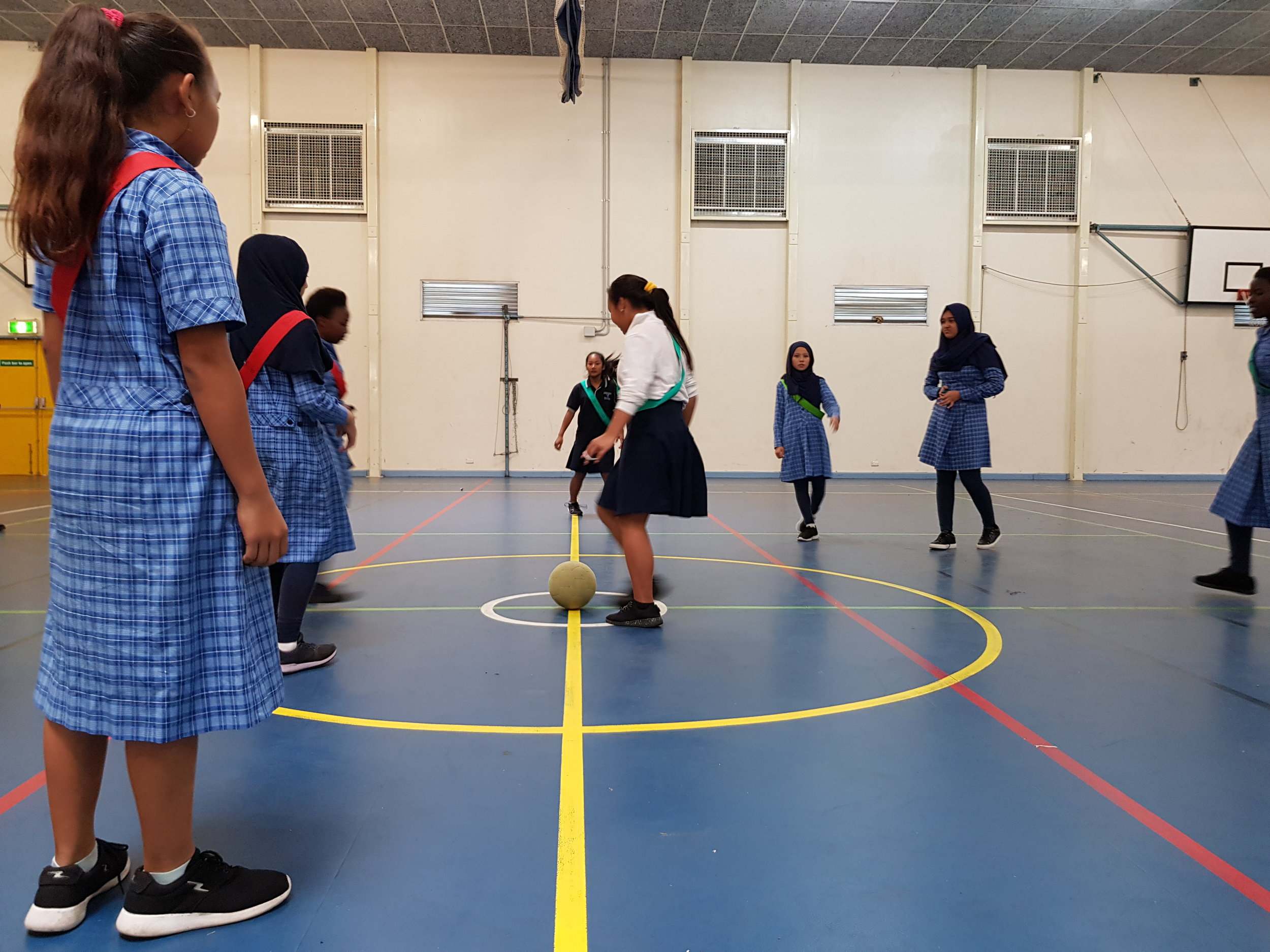 students playing soccer in the school gymnasium