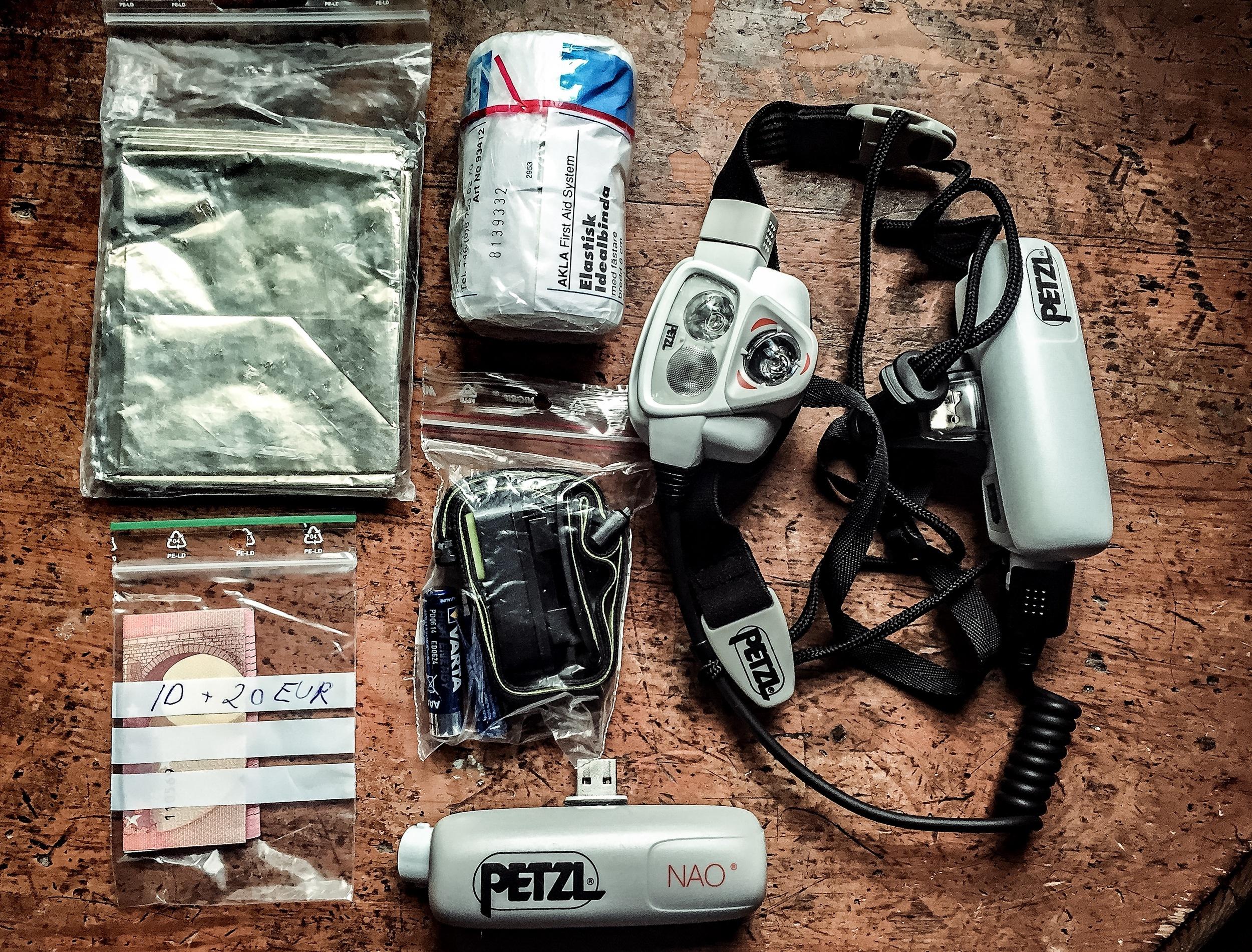 Räddningsfilt, elastisk binda, 20 EUR, lilla pannlampan ION från Black Diamond plus extrabatterier till denna, stora pannlampan Petzl NAO plus extrabatteri till den. Saknas på denna bild: mobiltelefon och ID-kort (ska sen ligga i samma påse som de 20 EUR man måste ha med sig).
