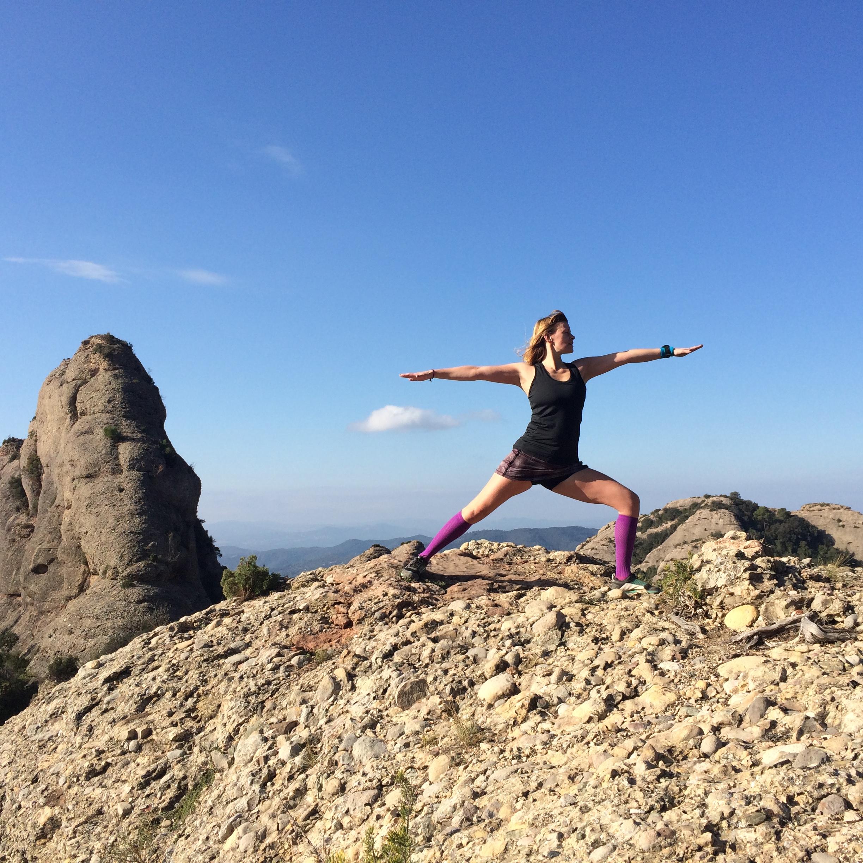 Yoga lyckas ofta få med både styrka, rörlighet och mentalt fokus i en och samma övning. Här yogar Mirja på en bergstopp i bergsmassivet Montserrat under vårt Ultra Trail Camp Montserrat 2015.