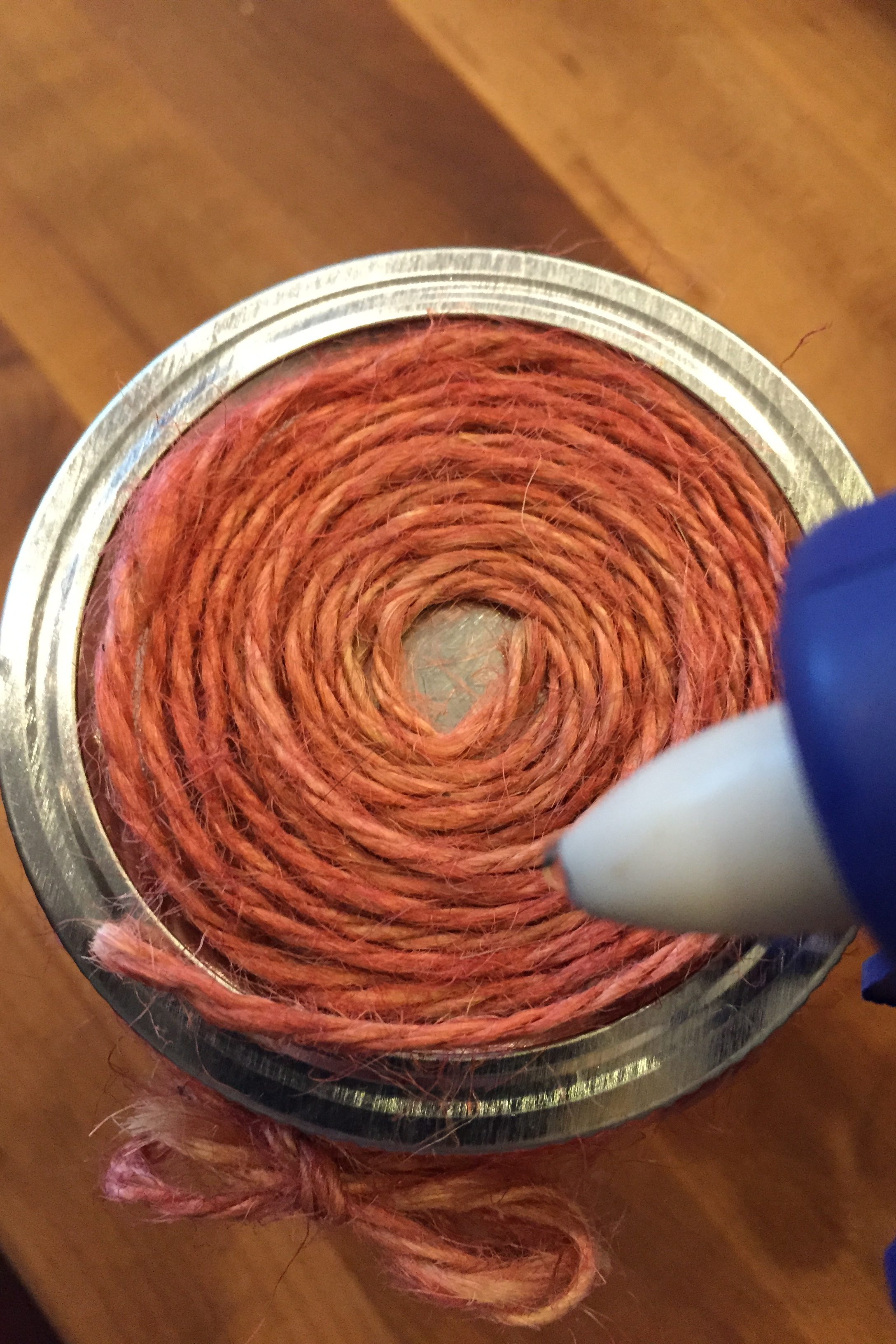 2. Use a touch of glue from a hot glue gun to secure the loose end over top of the spiral. Carefully remove spiral off of top and place aside until step 4.