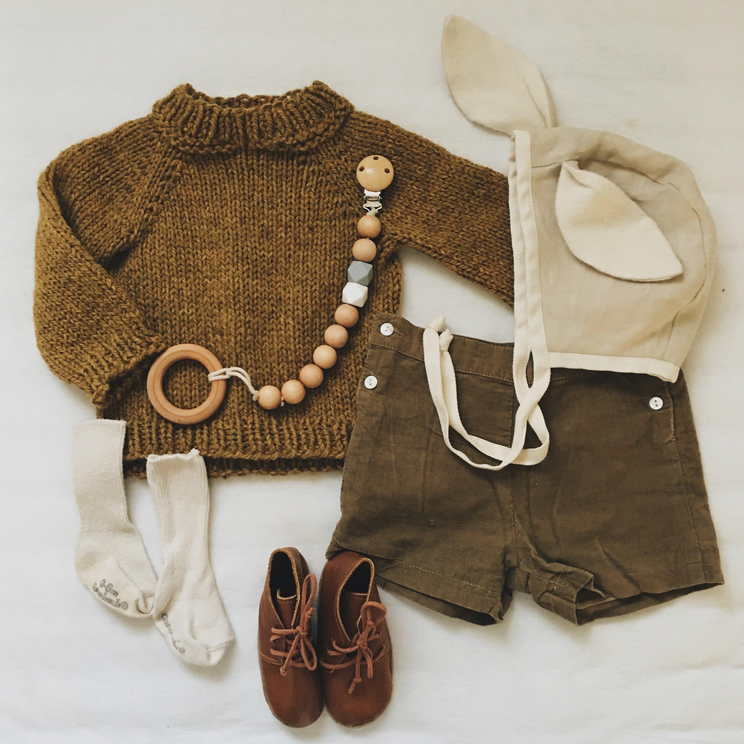 Fisherman's Sweater c/o  A Little Sweater Shop  ; Shorts c/o  Bubala Kids  ;  Linen Rabbit-eared Bonnet  c/o  Tortoise and The Hare Clothing  ;  Leather Booties  c/o  Ulla + Viggo ;  Pacifier Clip  c/o  Wild Creek Co