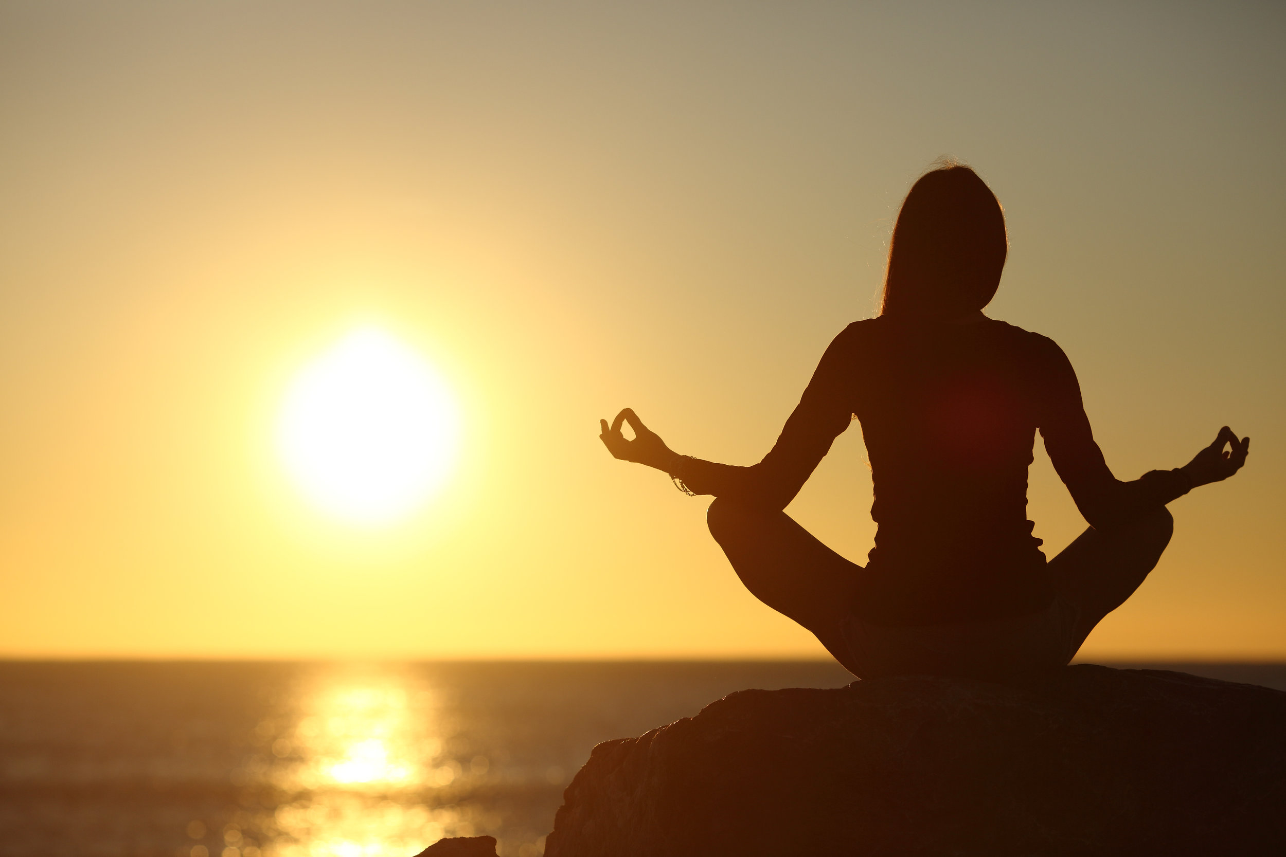 Woman meditating and practicing yoga watching the sun.jpg