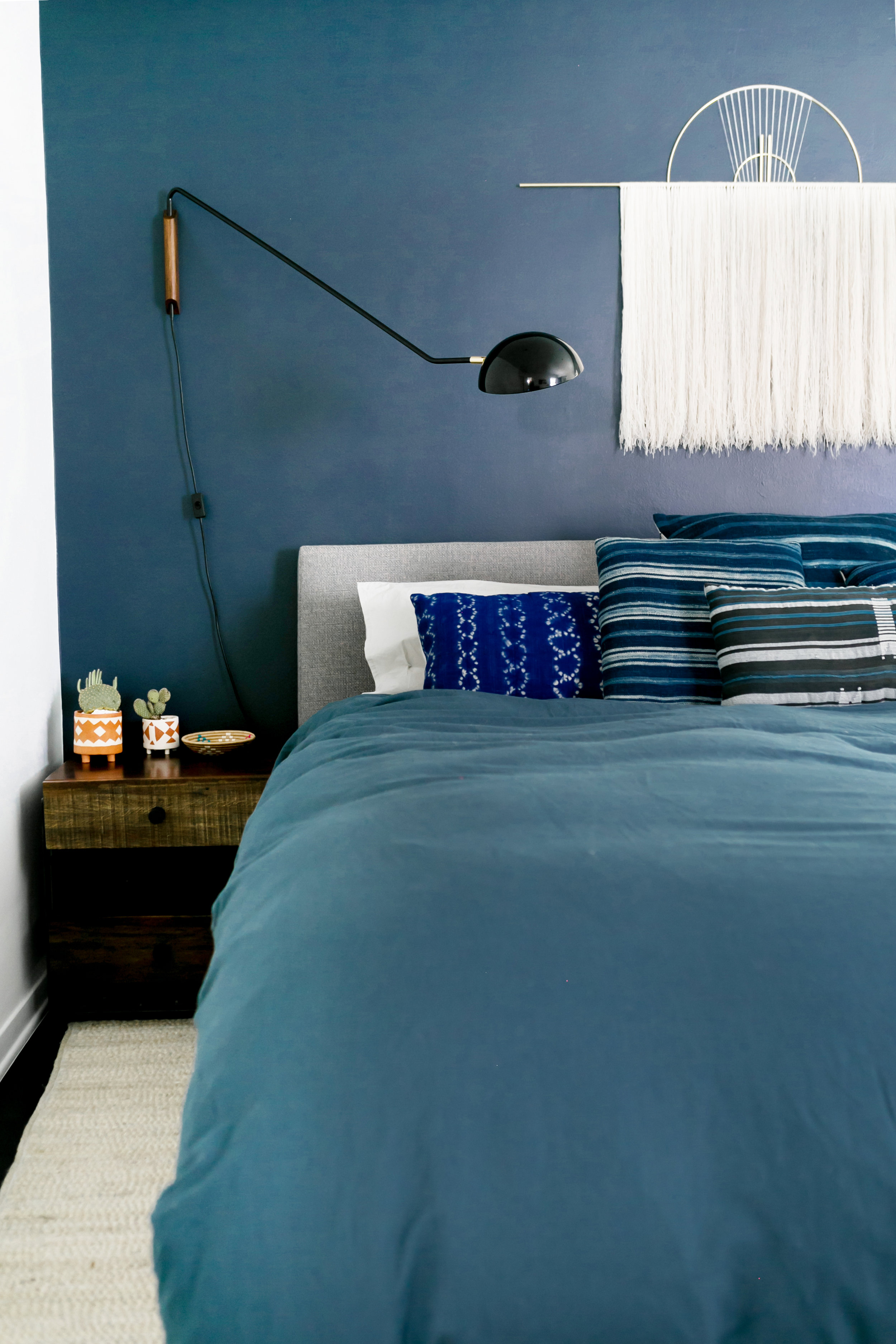 The Master Bedroom - My husband urged me to skew slightly masculine when it came to the master bedroom.We paired High Fashion Home's Hansen Bed and Hauser side table with navy and shibori accents including our wall,which is painted