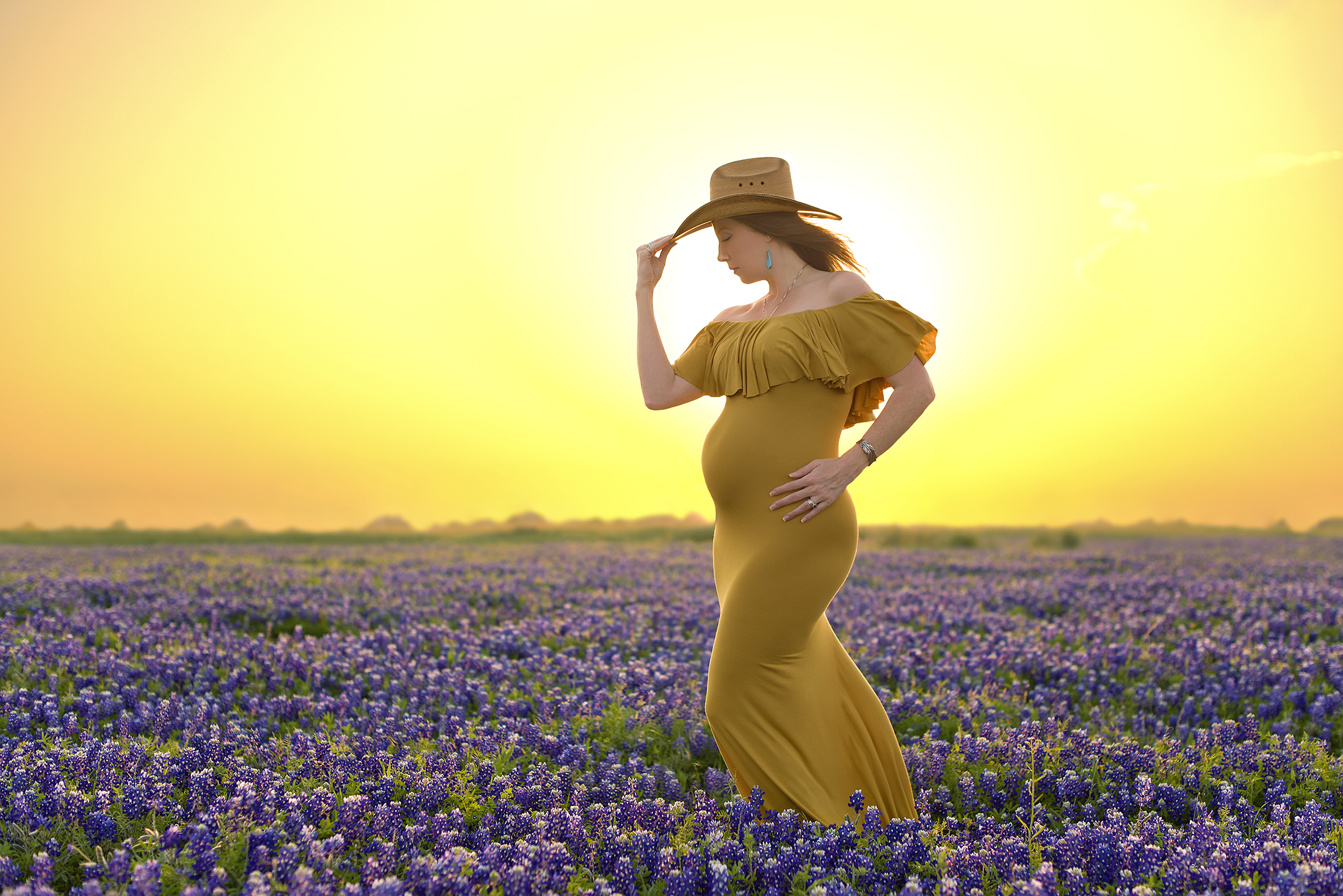 golden backlit maternity in cowboy hat