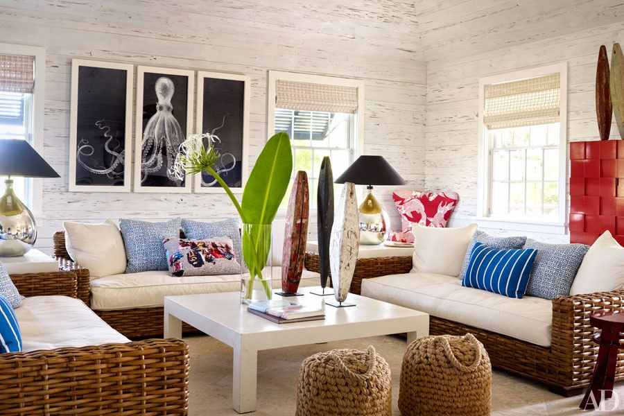 Love the rattan, washed out white wood walls, woven wood blinds, and large tropical arrangement.