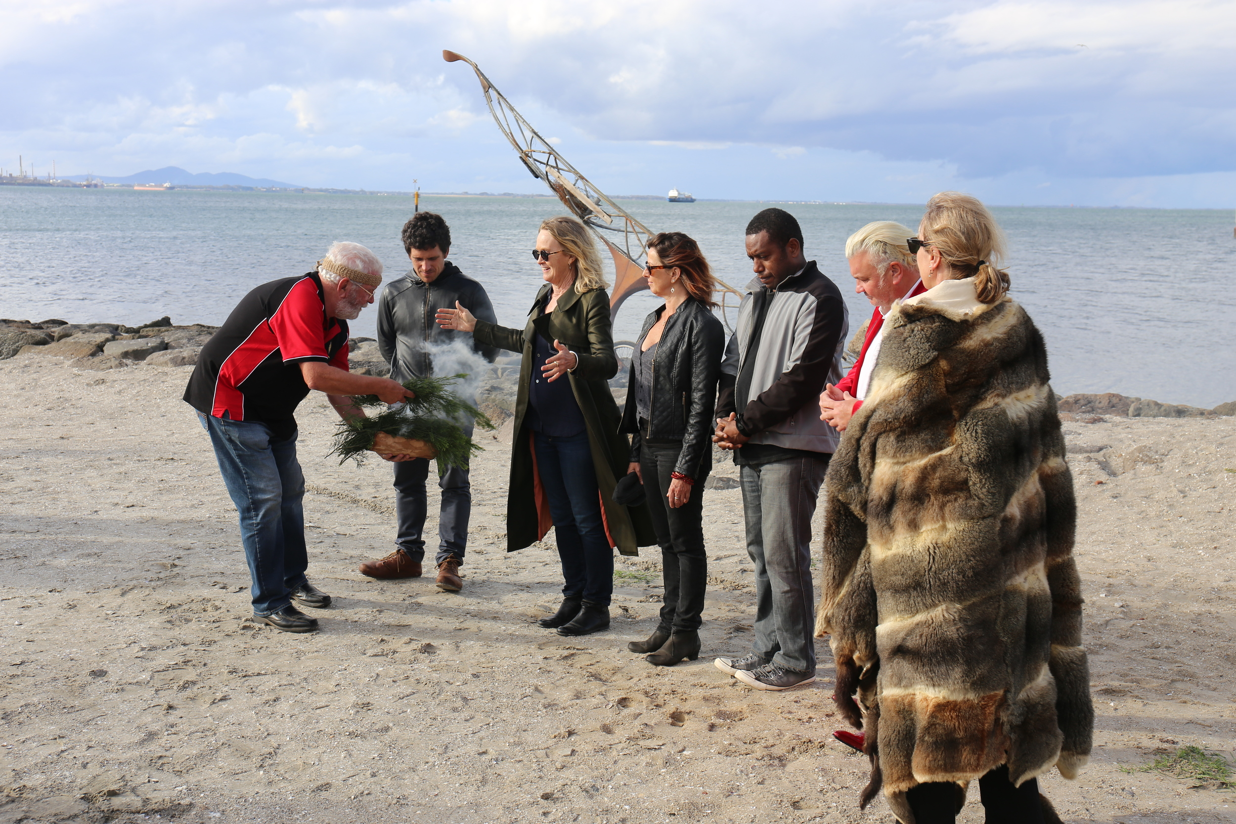 Wadawurrung Elder Uncle Bryon Powell smoking 2014 Canoe artist Benjamin Gilbert, Mountain to Mouth Artistic Director Meme McDonald, Mahony Maia Kiely, Leonard Tebegetu, Mayor Darryn Lyons and Manager of Arts and Culture Kaz Paton at the  Eastern Beach ceremony.