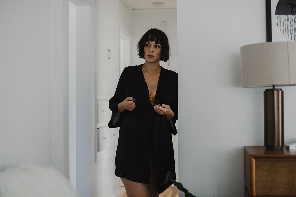 woman tying black robe in hallway