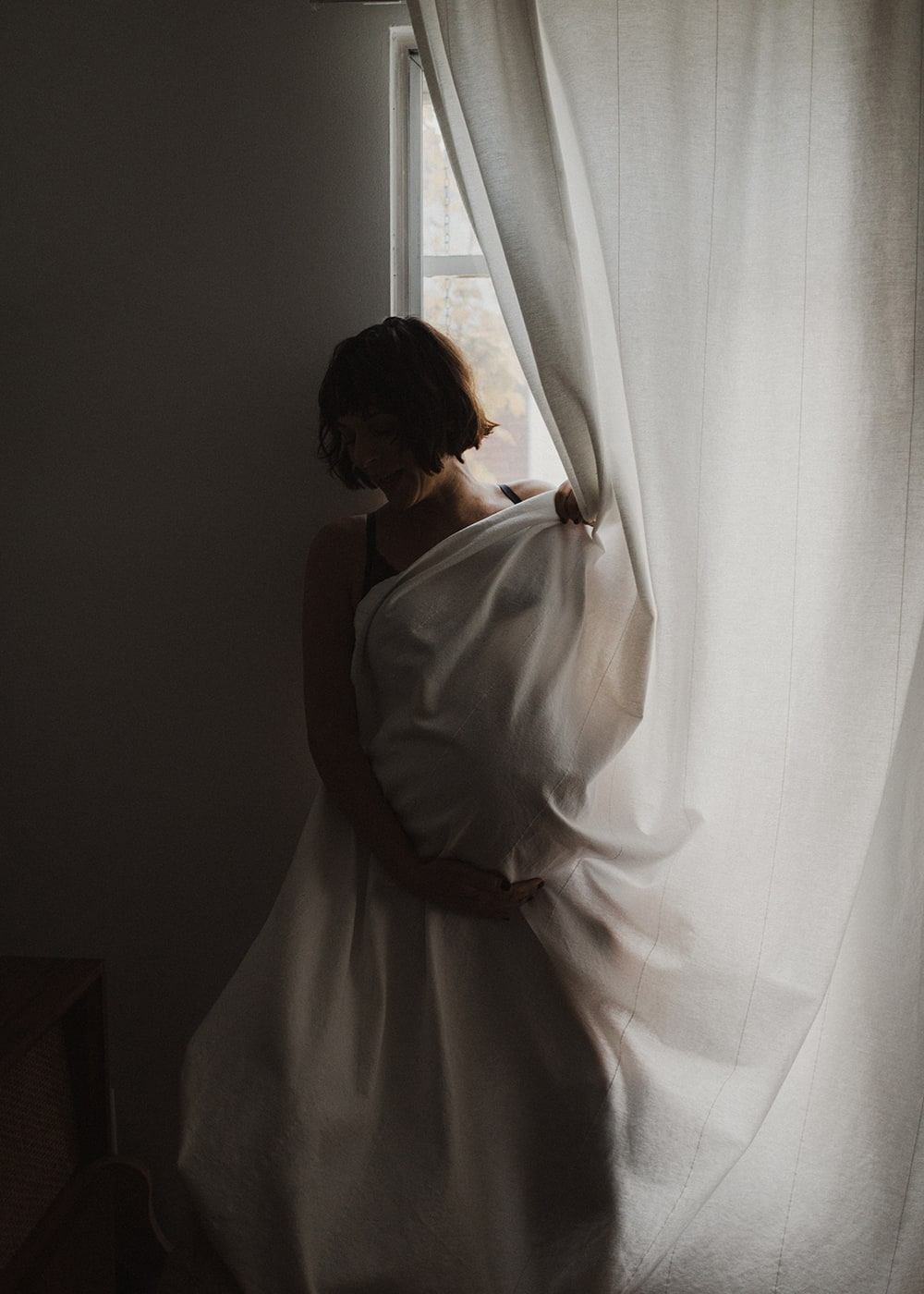 woman cuddling in window with curtains