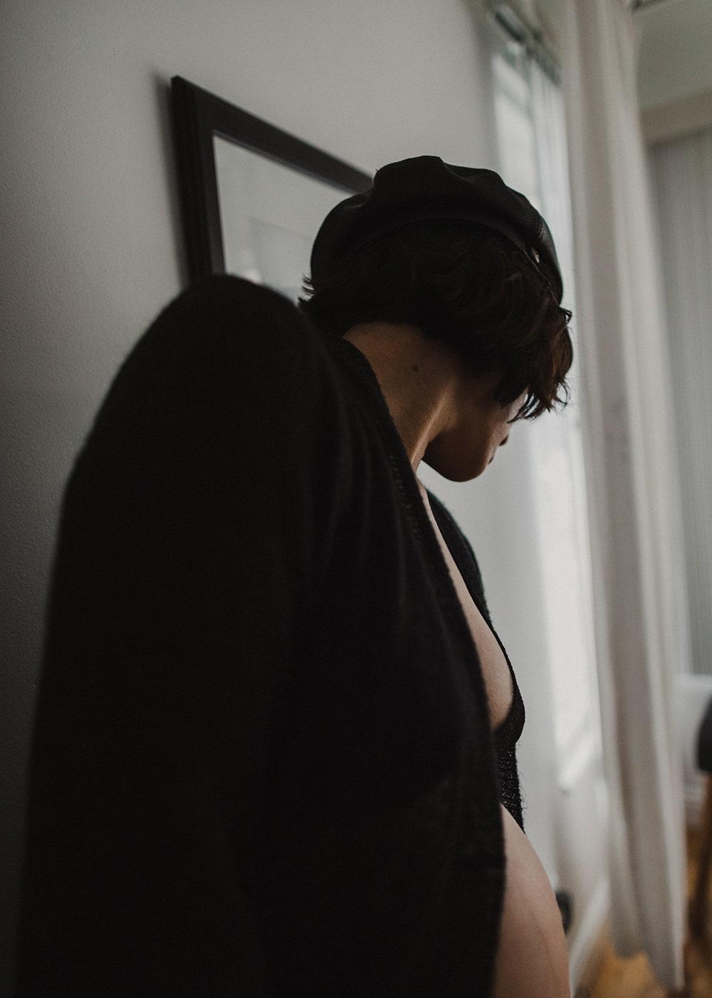 woman wearing hat looking down at window