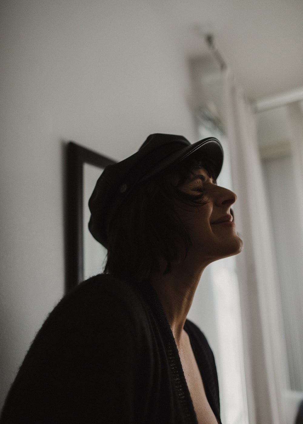 woman wearing hat looking up and smiling