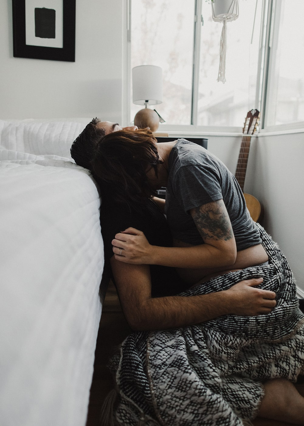 man and woman cuddling while woman's head sits on his shoulder