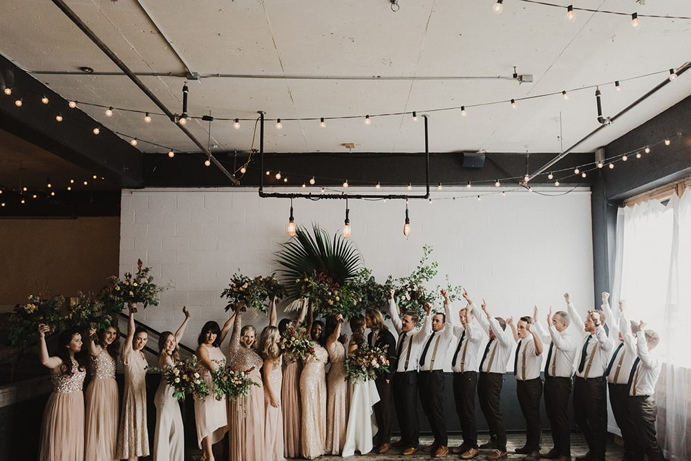 bridesmaids and groomsmen celebrating for photographer